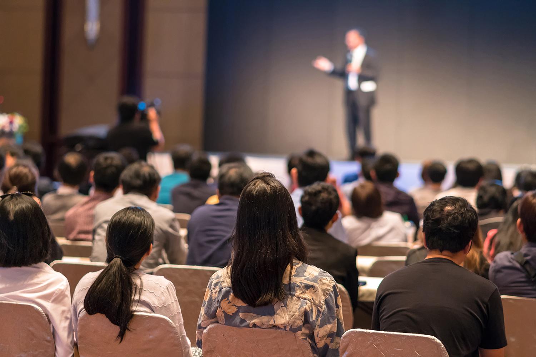 Decreto Riaperture: la rabbia dell'industria dei congressi e degli eventi. Nell'immagine, persone ad un congresso intente ad ascoltare lo speaker