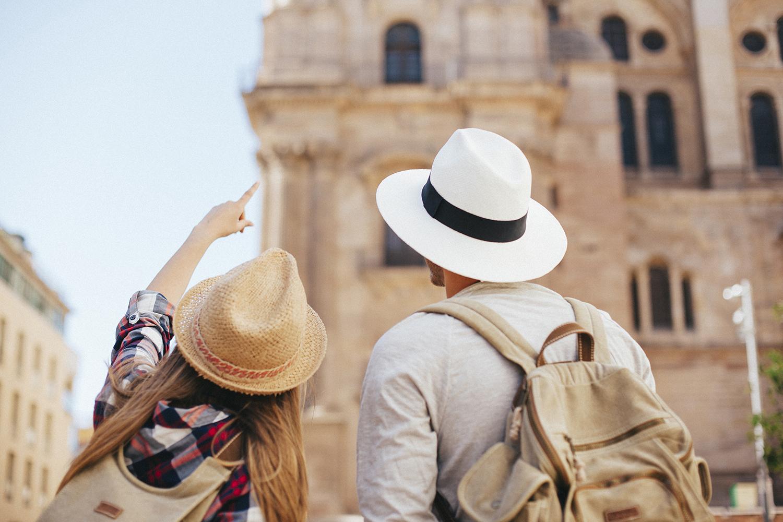 I turisti stranieri tornano a prenotare le vacanze in Italia. Nella foto, due turisti di spalle che indicano un monumento storico italiano.