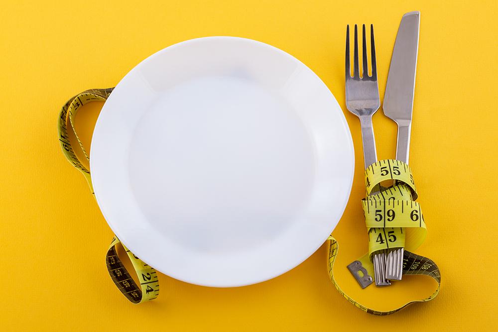 Cucina sartoriale: un piatto vuoto accanto ad un metro da sarto. Immagine per l'editoriale di Elsa Mazzolini sulla cucina sartoriale
